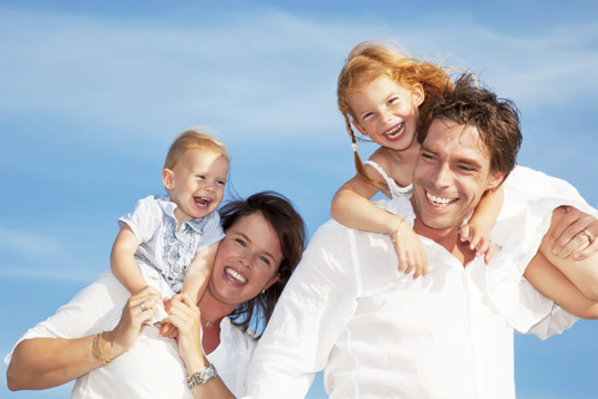 happy man with full head of hair with his family on the beach